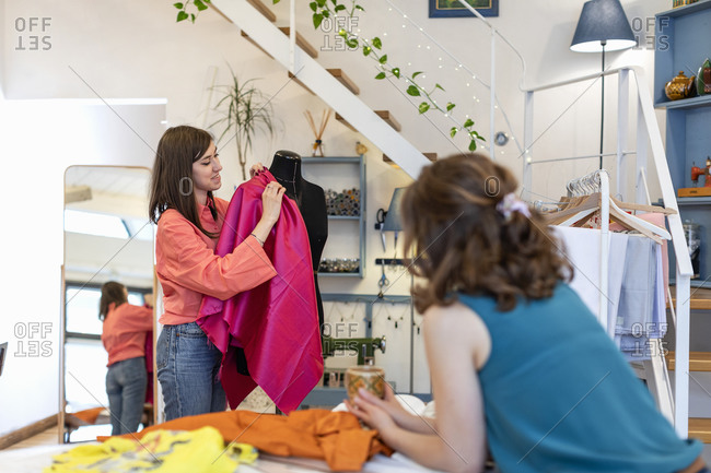 Fashion designer looking at smiling young trainee holding fabric on dummy in atelier