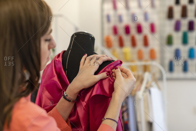 Close-up of young female fashion designer dressing mannequin at design studio