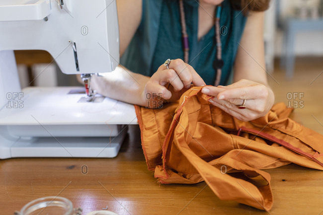 Female seamstress sewing orange fabric at atelier