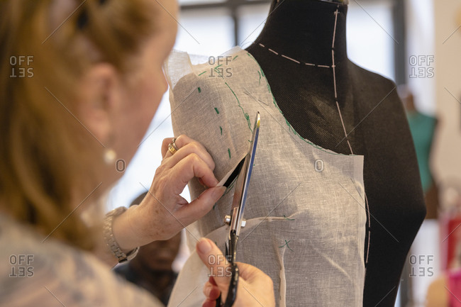 Close-up of senior designer cutting fabric on mannequin with scissors in atelier