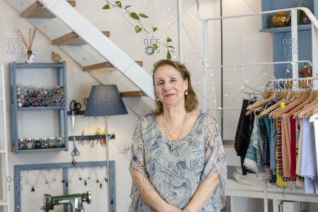 Smiling senior female design professional standing at illuminated fashion studio