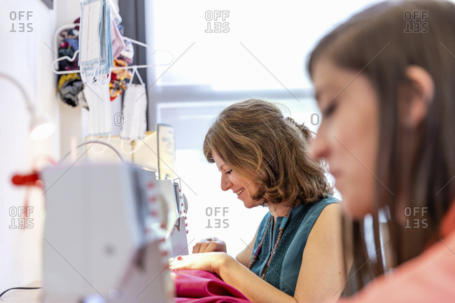 Smiling seamstress sewing by coworker at design studio
