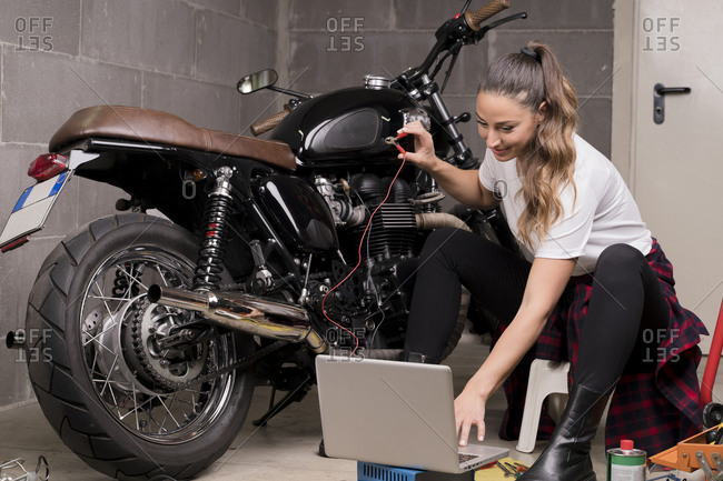 Young woman using laptop and checking motorbike