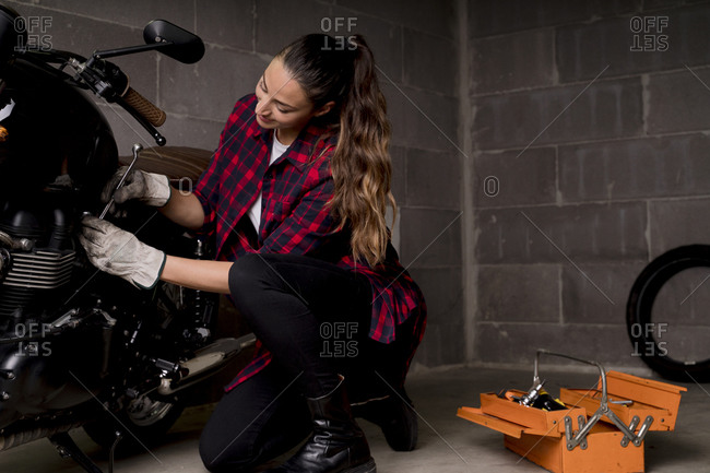 Woman repairing motorbike - Offset Collection