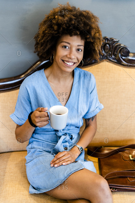 Happy young woman with afro hairstyle holding coffee mug in modern cafe