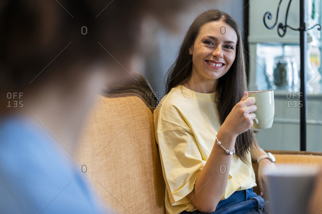 Happy woman holding coffee mug while looking friend in coffee shop