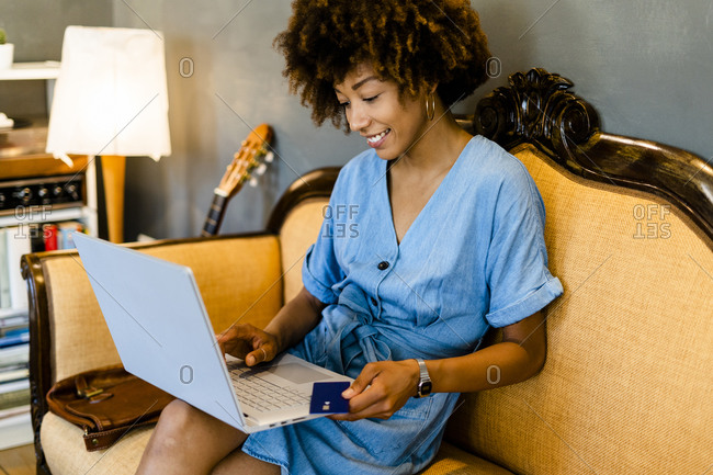 Happy woman using credit card and laptop while shopping online in cafe