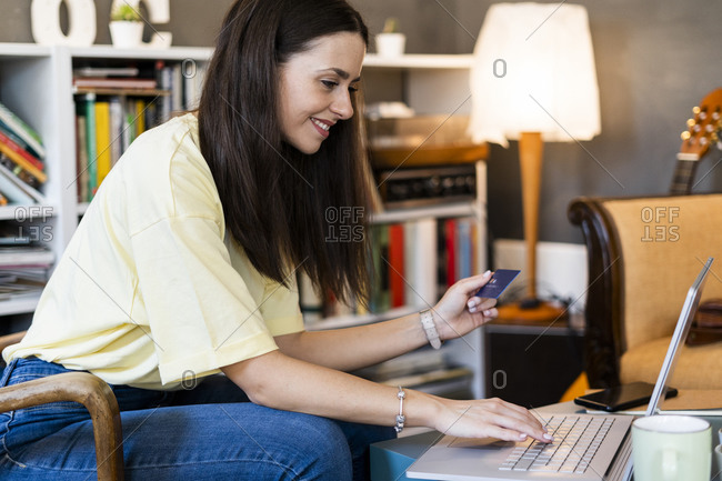 Beautiful woman using credit card and laptop while shopping online in cafe