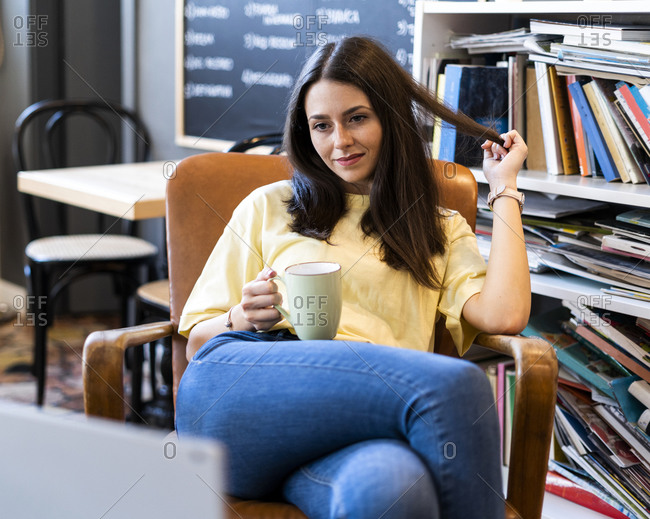 Beautiful young woman holding coffee mug while sitting on armchair in coffee shop