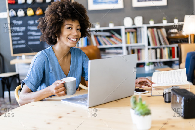 Thoughtful woman holding coffee mug while sitting with laptop at cafe table
