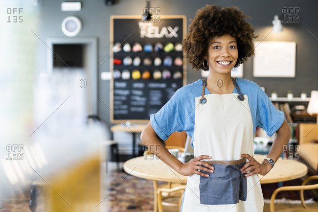 Confident female owner standing with hands on hips at coffee shop