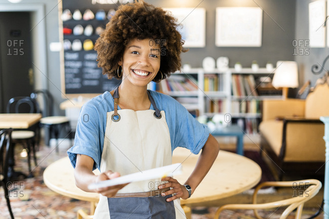 Happy female owner giving menu while standing with hand on hip at coffee shop