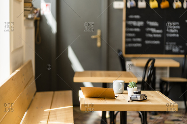 Book and camera on wooden table in modern coffee shop