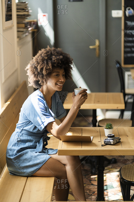 Thoughtful woman holding coffee mug while sitting at table in cafe