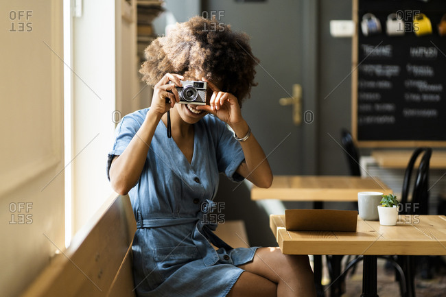 Happy young woman using digital camera while sitting in coffee shop
