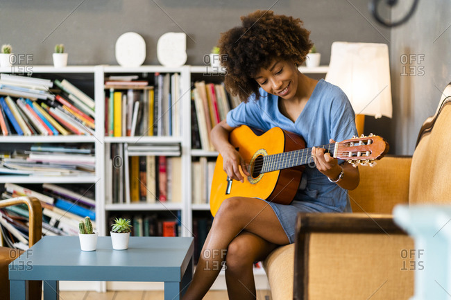 Happy woman playing guitar while sitting on sofa in coffee shop
