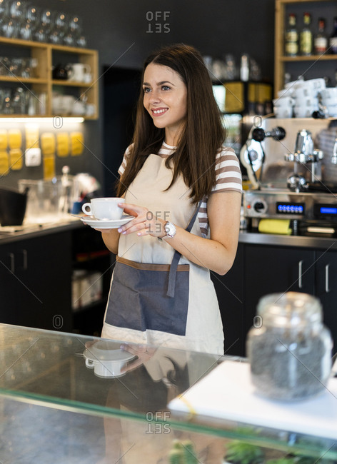 Happy female owner holding coffee cup and saucer while standing at counter in cafe
