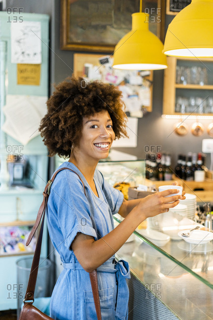 Happy young woman holding coffee cup while standing at counter in coffee shop