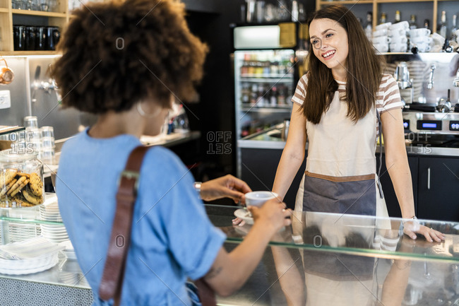 Happy female owner selling coffee to woman in coffee shop