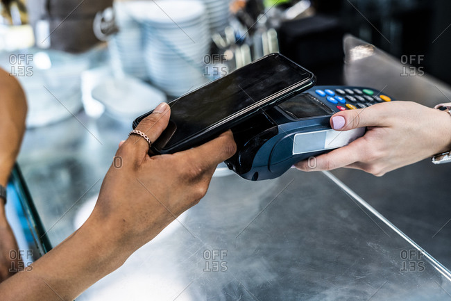 Female customer making contactless payment through smart phone in coffee shop