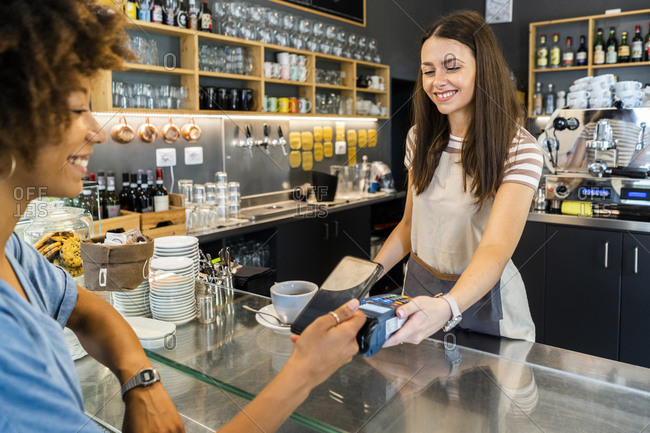 Happy female owner receiving contactless payment through smart phone from customer in coffee shop