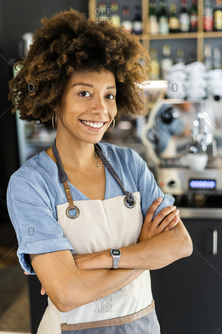 Confident female barista standing arms crossed in cafe