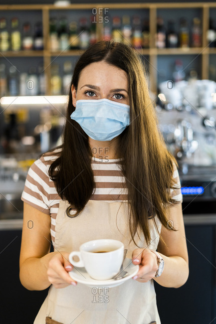 Beautiful young owner wearing mask while holding coffee cup and saucer in cafe