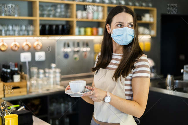 Thoughtful young owner wearing mask while holding coffee cup and saucer in cafe