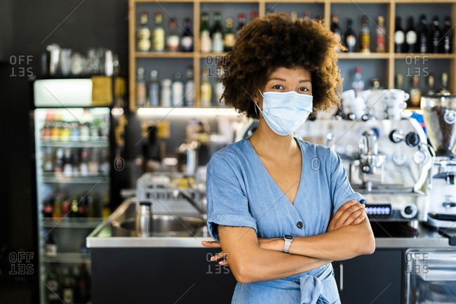 Confident female owner wearing mask while standing arms crossed in coffee shop
