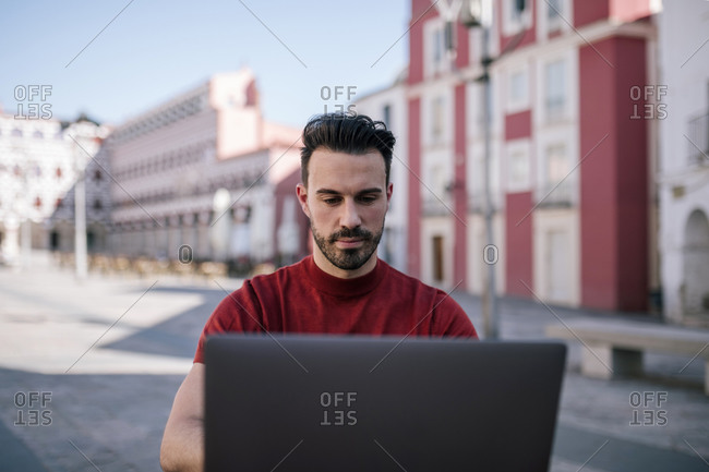 Handsome man using laptop in city