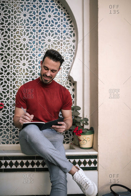 Smiling man writing in book while sitting on window sill