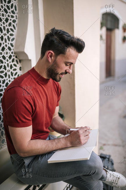 Handsome businessman writing in book while sitting on window sill