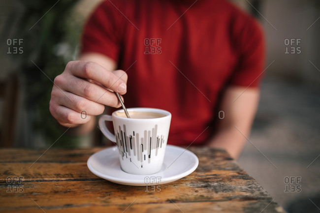 Close-up of man's hand stirring coffee while sitting at sidewalk cafe