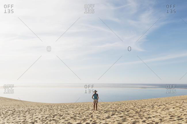 Woman looking at Atlantic ocean while standing on beach during sunny day- Nouvelle-Aquitaine- France