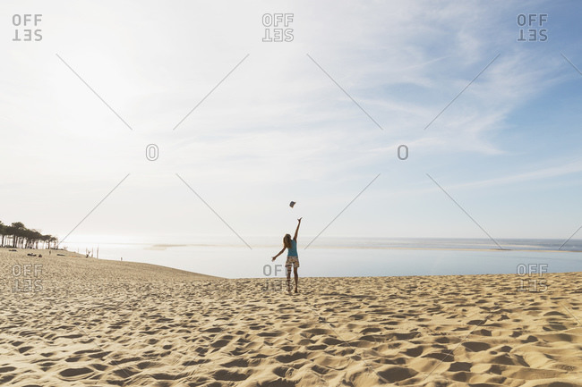 Happy woman throwing hat in mid air while standing at beach against sky- Nouvelle-Aquitaine- France
