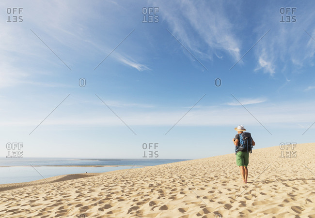 Senior man with backpack looking at Atlantic ocean while standing on beach- Nouvelle-Aquitaine- France