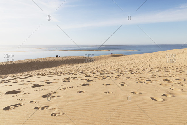 Scenic view of Pilat dunes and Atlantic ocean against sky during sunny day- Nouvelle-Aquitaine- France