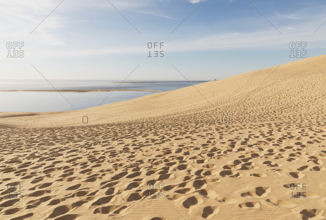 Dune of Pilat by Atlantic ocean against sky on sunny day- Nouvelle-Aquitaine- France