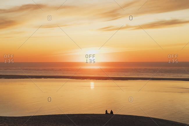 Silhouette couple watching sunset at Atlantic ocean- Nouvelle-Aquitaine- France