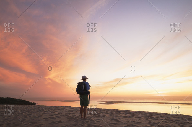 Senior man with backpack looking at Atlantic ocean against sky during sunset- Nouvelle-Aquitaine- France