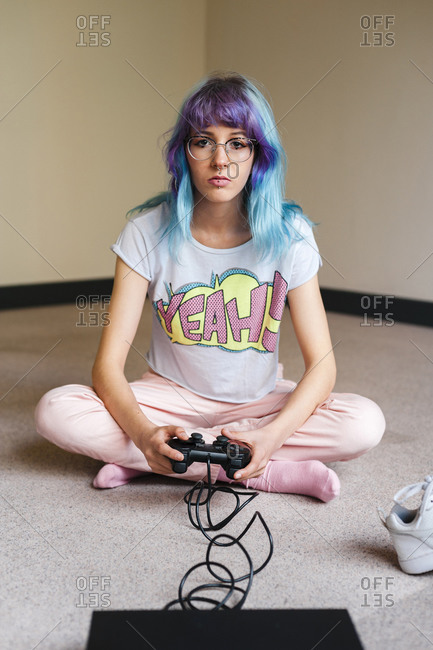 Trendy blue haired woman playing video game at home