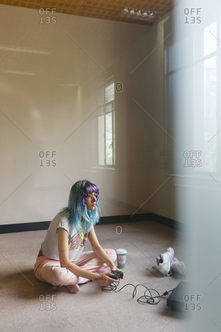 Trendy blue haired woman playing video game on floor at home