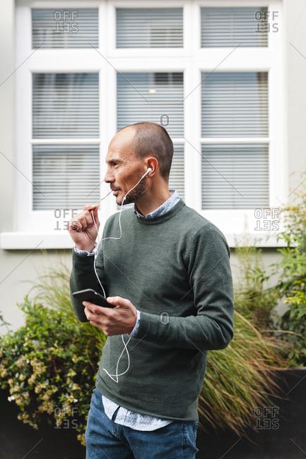 Mature man talking through in-ear headphones against window in city