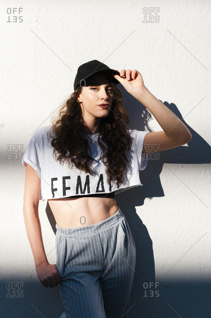 Fashionable young woman standing against white wall during sunny day