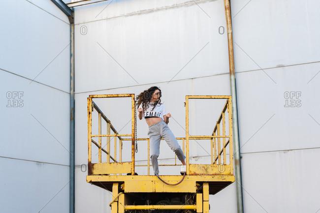 Female hip-hop dancer dancing on metallic platform in abandoned building
