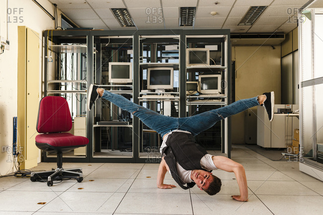 Male dancer performing stunt on floor in abandoned room