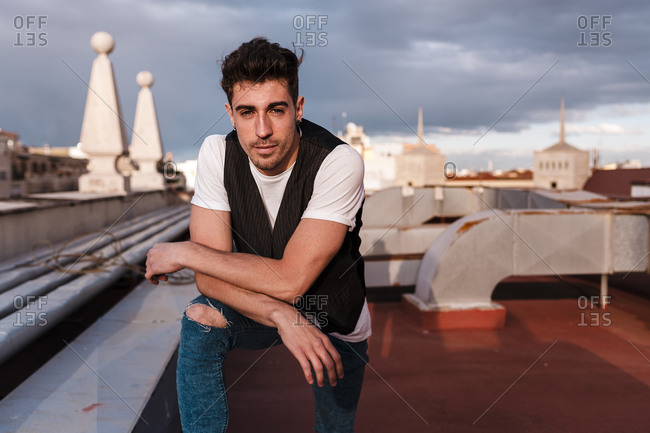Handsome young man standing on abandoned building terrace against cloudy sky in city