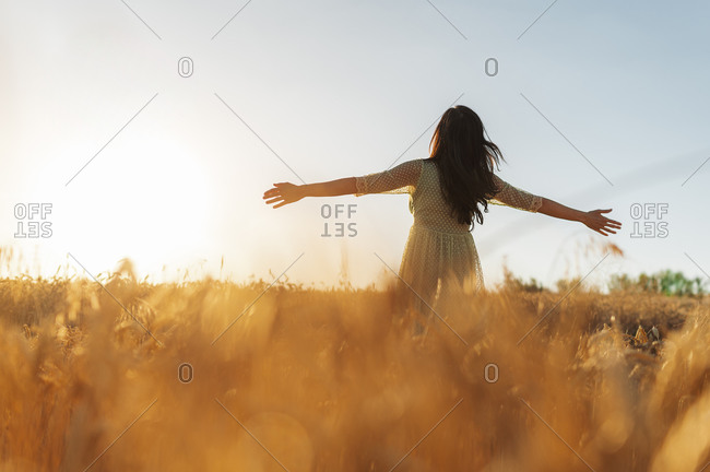 Young woman with arms outstretched standing amidst wheat farm against clear sky during sunset