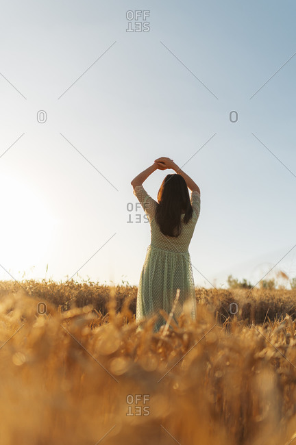 Young woman with arms raised standing amidst wheat farm against clear sky during sunset