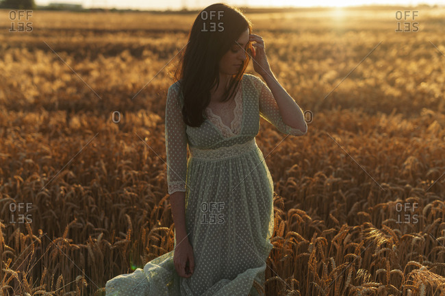 Young woman wearing dress standing amidst wheat crops in farm during sunset